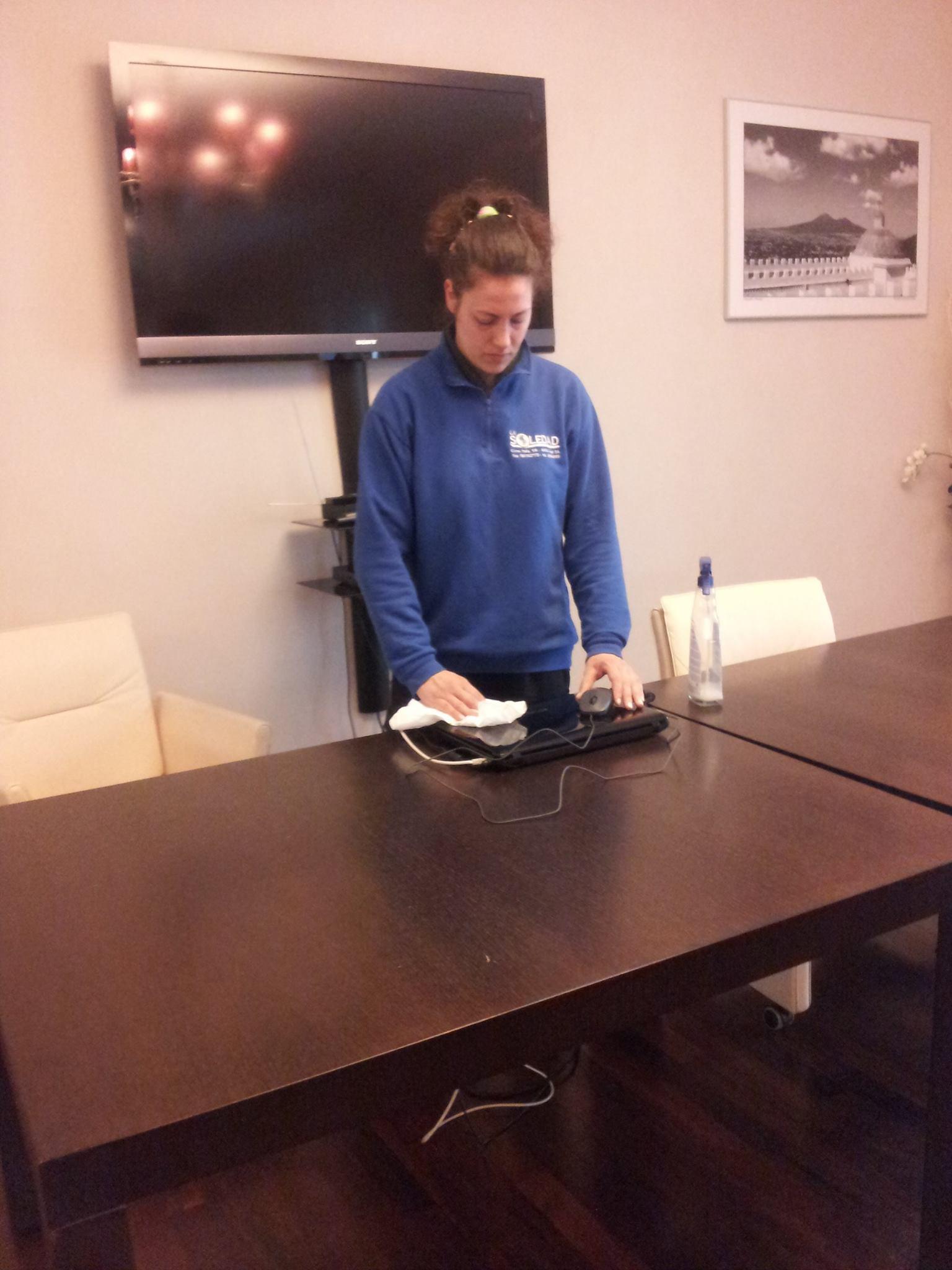 Ragazza mora con felpa blu mentre pulisce tavolo