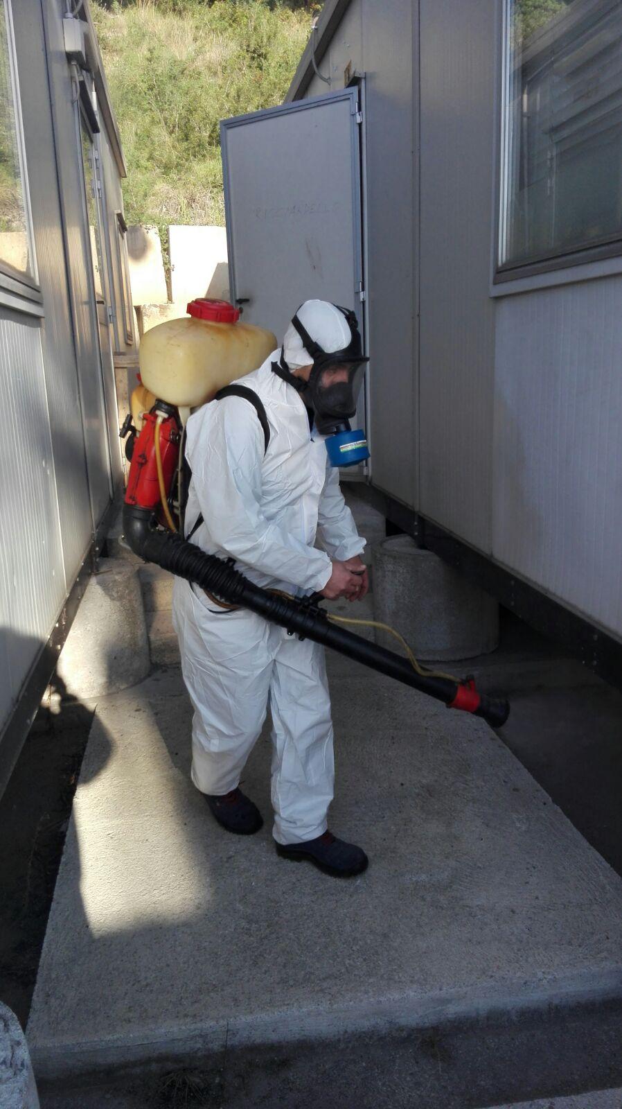 Uomo con tuta bianca mentre spruzza liquido da tanica