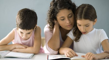 Lady helping two kids with homework