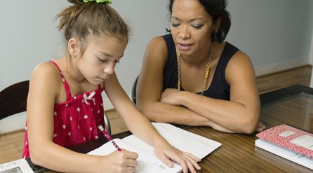 Mother helping her daughter study