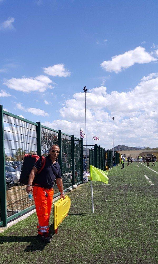 un soccorritore vicino a una bandierina in un campo da calcio