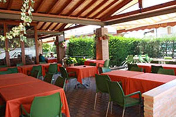 serie di tavoli con tovaglie arancioni e sedie verdi all'aperto sotto una tettoia in legno