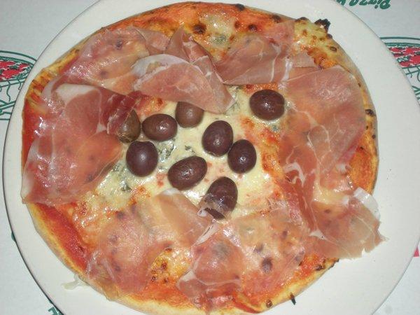 pizza con prosciutto e olive nere al centro