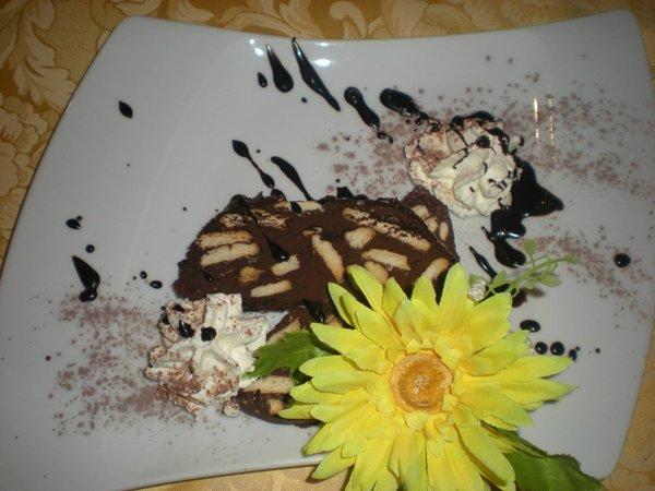 dolce con schizzi di cioccolato panna e un fiore giallo