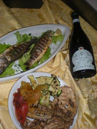 piatto a base di pesce con verdure miste alla griglia e bottiglia di vino