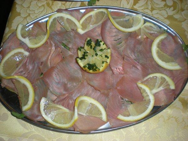 vassoio di carne cruda tagliata sottiole con spicchi di limone