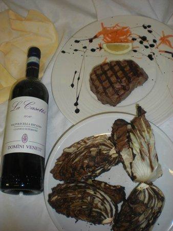 piatto di carne con verdure grigliate accompagnate da una bottiglia di vino