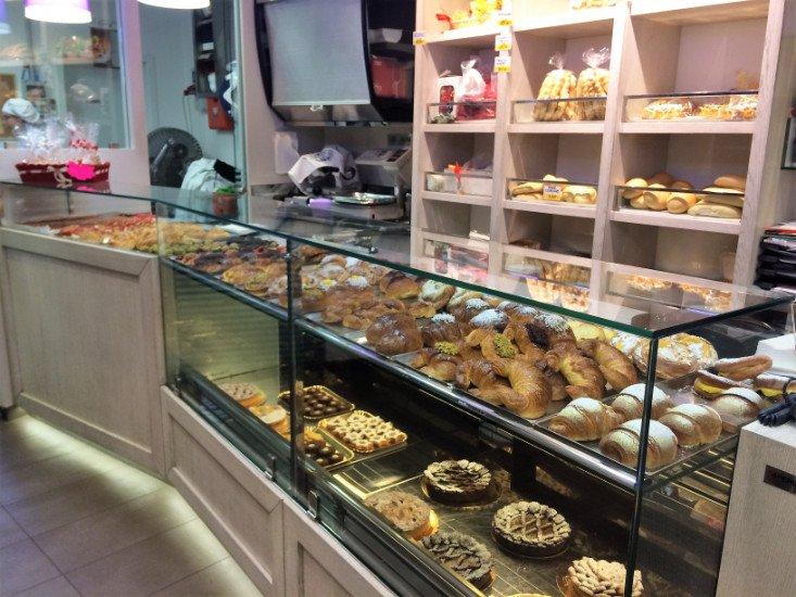 Dei scaffali con varie tipi di pane e una vetrina con delle torte