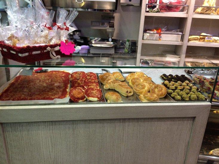 una vetrina con tranci di pizza, pizzette e dei pasticcini