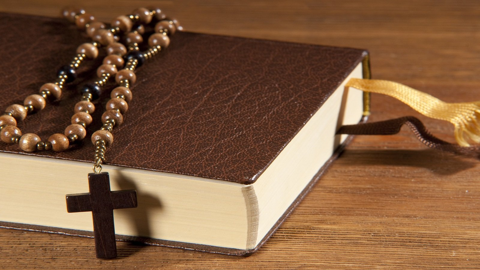 un libro marrone e un rosario