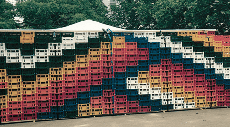 artfully arranged stack of red, pink, orange, green, blue and white crates
