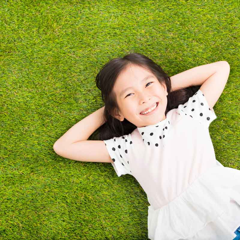 little girl smiling on grass