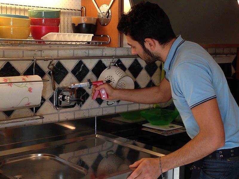 uomo mentre incolla un pomello in cucina con una pistola contenente colla