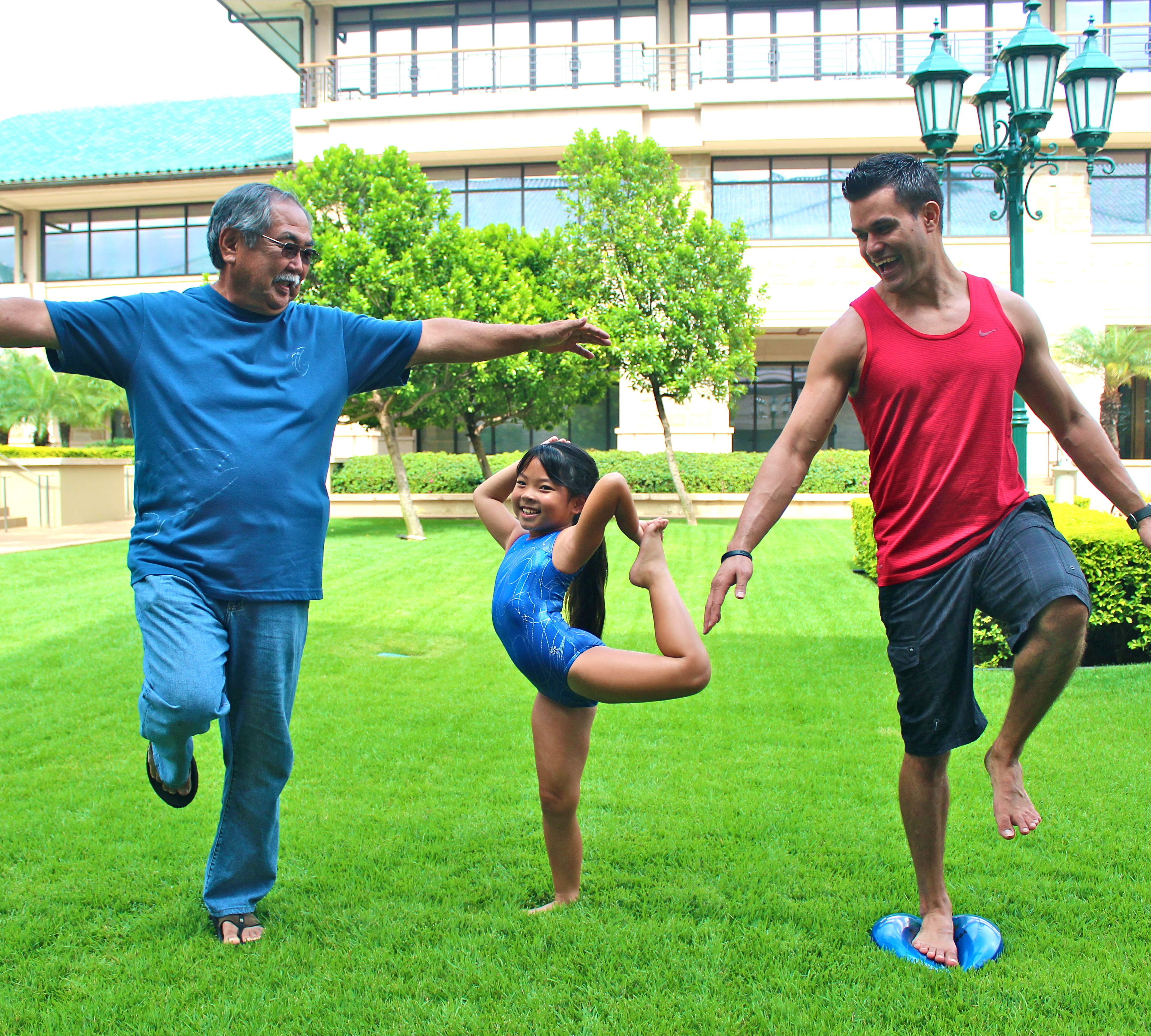 A little girl and two men balancing themselves doing exercise