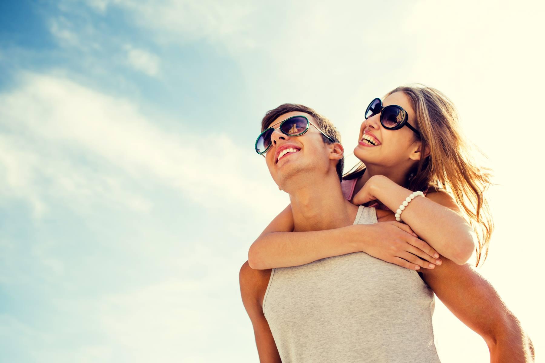 Una coppia sorridendo felice indossa belle occhiali da sole
