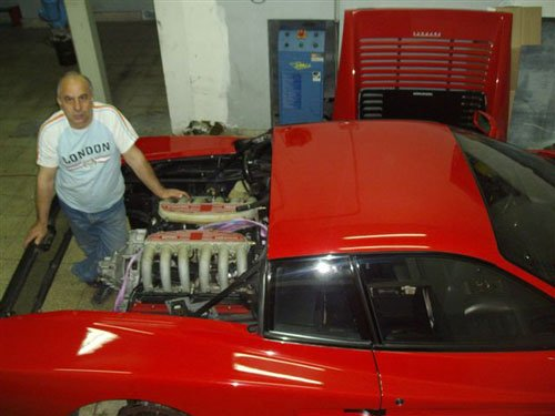 una Ferrari rossa col motore smontato vista e dietro un uomo con una t-shirt bianca in posa per una foto