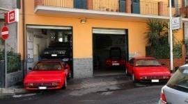 vista da lontano di due Ferrari Testarossa parcheggiate fuori da uno stabile arancione