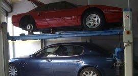 Una Ferrari Testa rossa sul ponte elevatore e sotto un'altra macchina blu