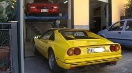 una macchina sportiva gialla vista da dietro e dentro all'officina una Ferrari Testarossa sul ponte elevatore