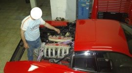 un uomo con la faccia censurata al lavoro e affianco una Ferrari Testarossa smontata