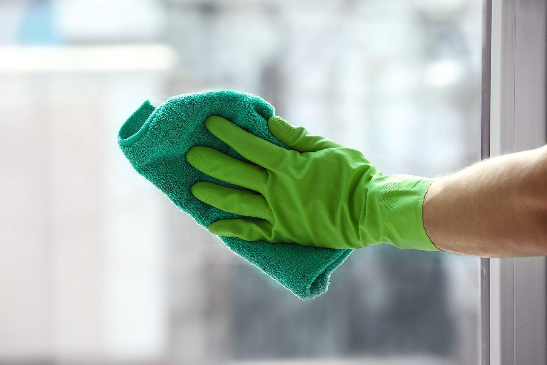 mano con guanto verde che pulisce il vetro