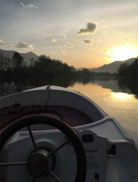 il volante di una barca e vista del lago e delle montagne