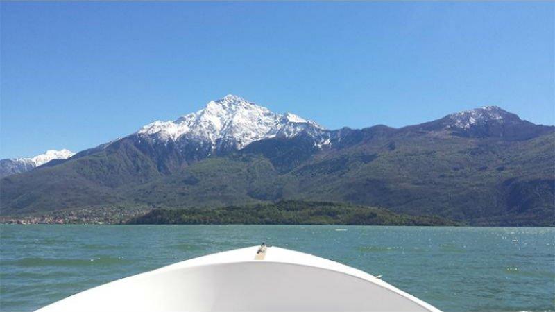 la prua di una barca e vista di una cima di una montagna innevata