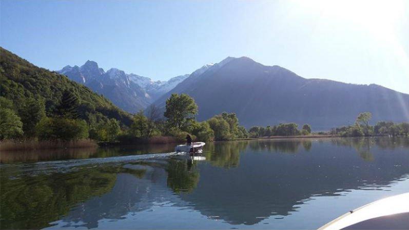 vista della barca del lago della vegetazione e delle montagne