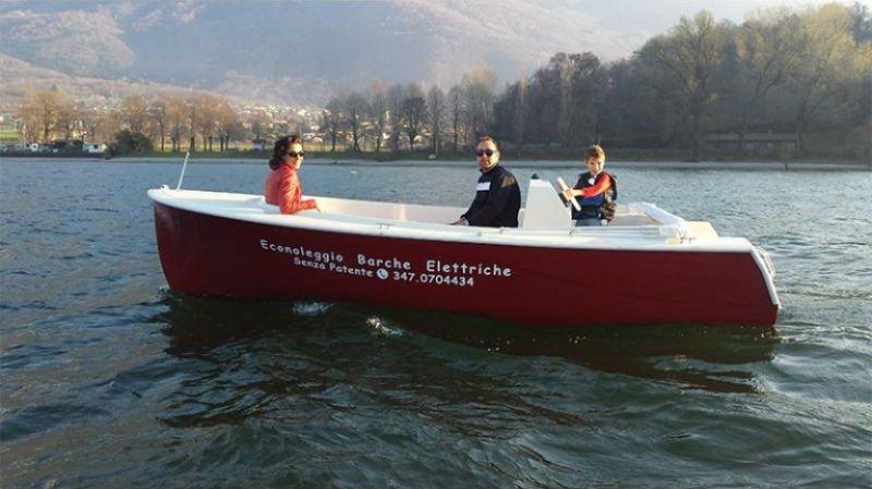 un uomo, una donna e un bambino su una barca rossa
