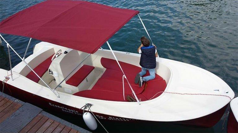 un bambino su una barca rossa con un tendalino