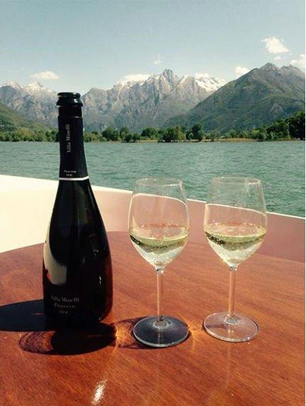 una bottiglia e due bicchieri di spumante su una barca