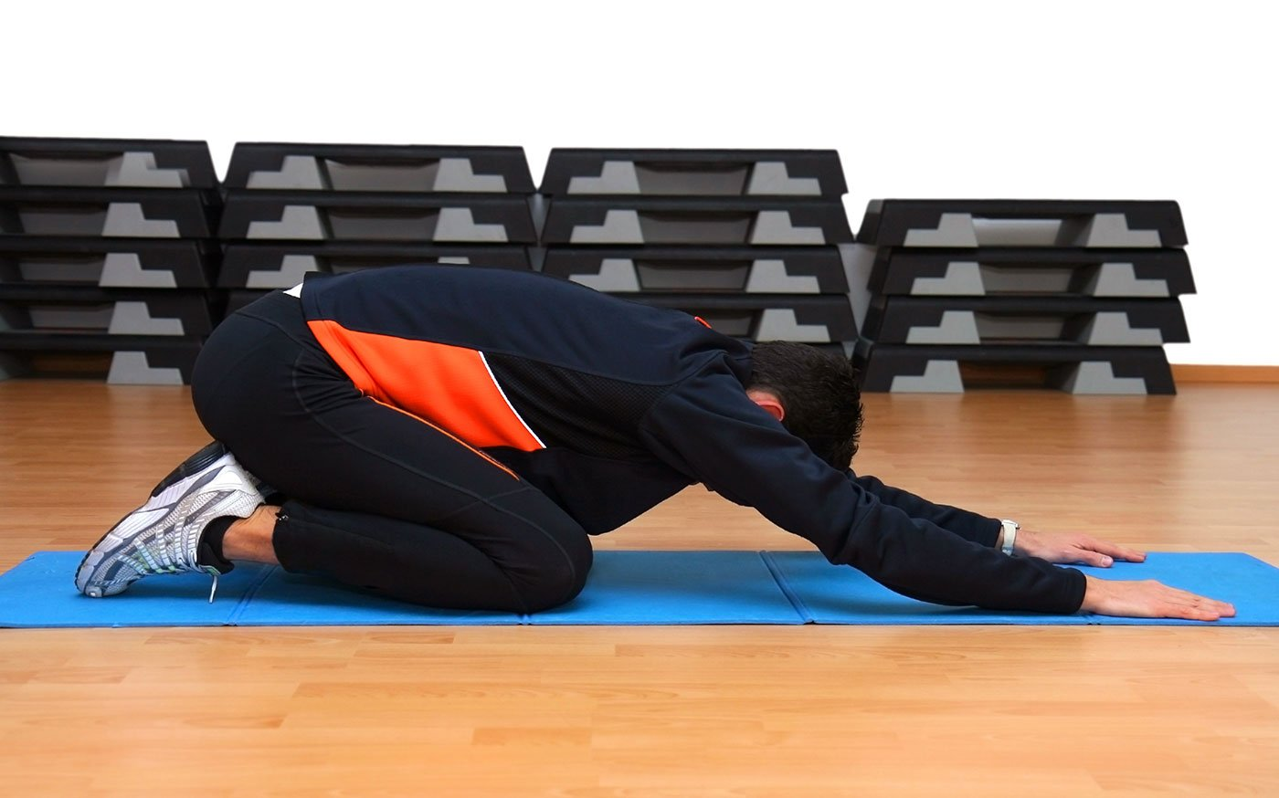 un ragazzo con una tuta blu che fa ginnastica su un tappetino
