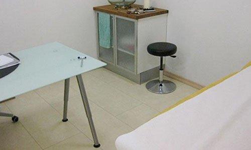 una scrivania di vetro un mobiletto e uno sgabello nero