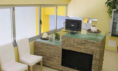 due sedie bianche e un bancone in pietra e vetro con un monitor