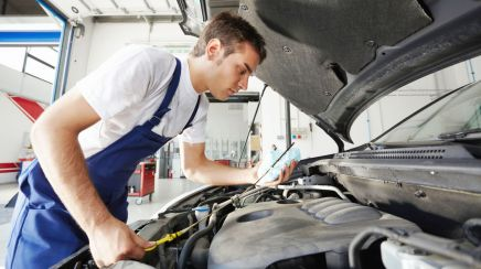 Mechanic checking the oil level during our engine repairs service in
