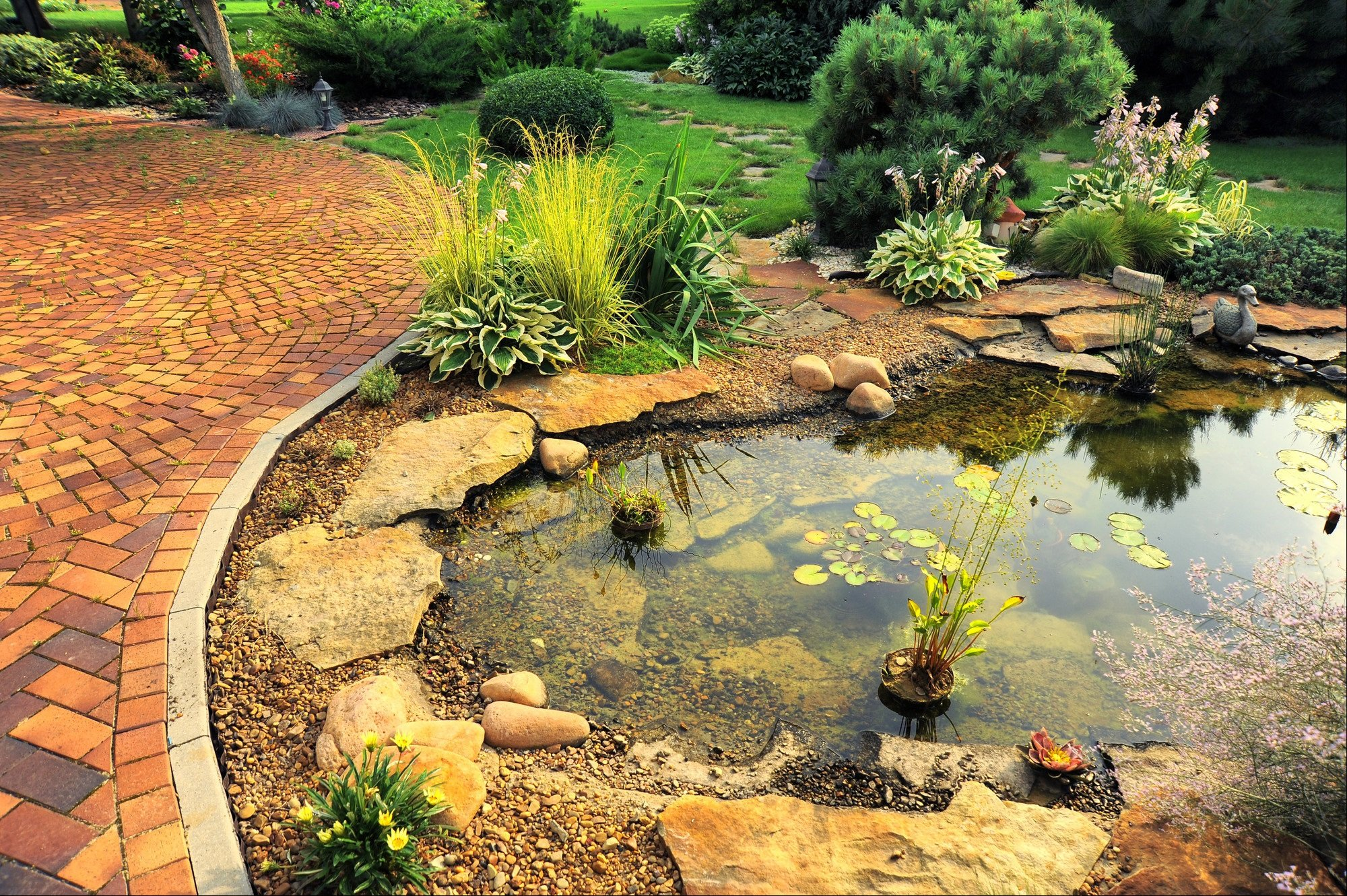 Terracotta paving around a garden pond
