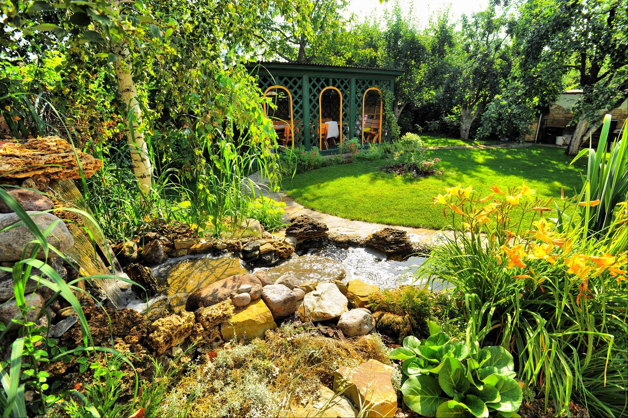 A green Summer house in a garden with curved lawn and water feature