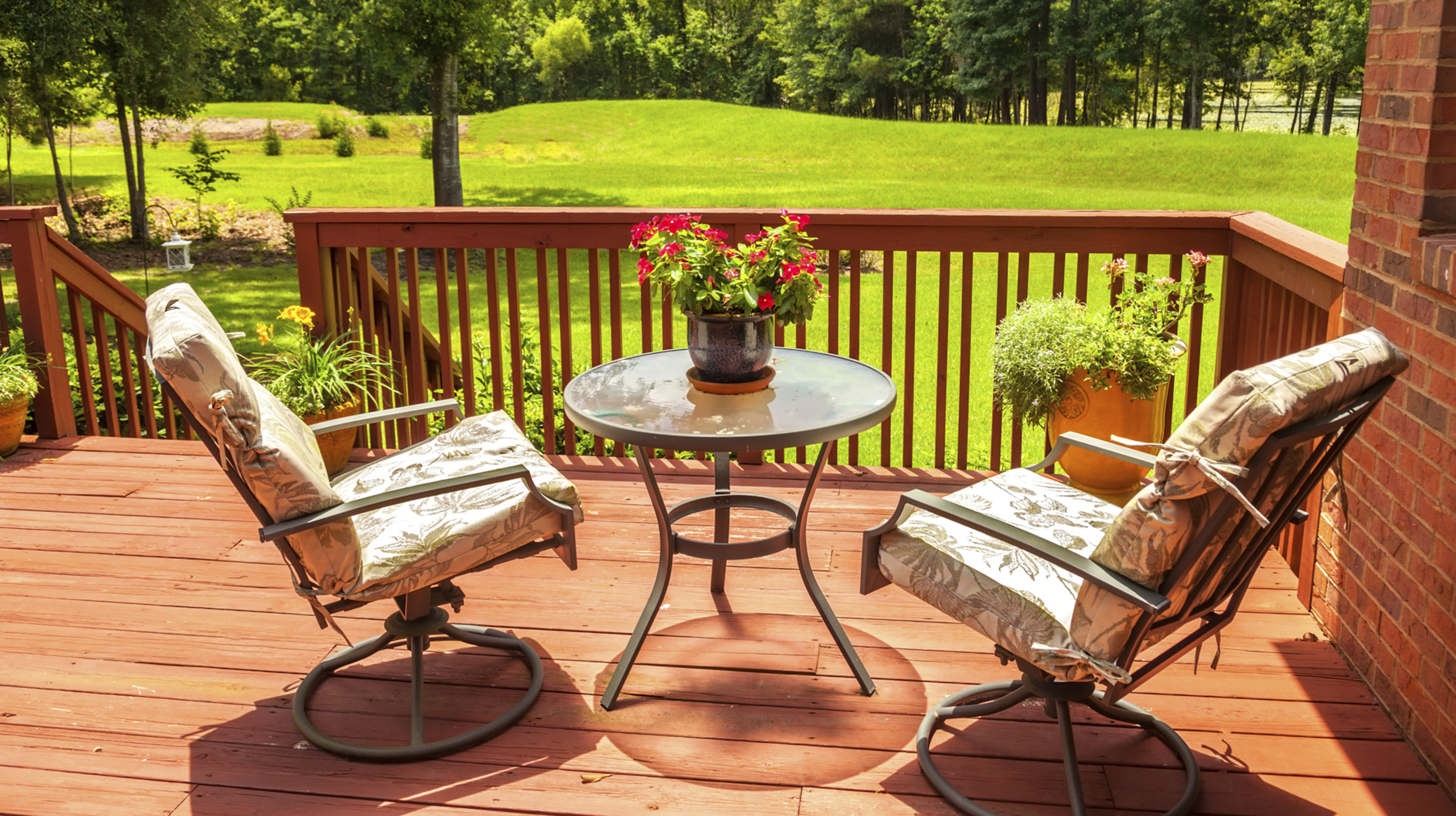 Garden chairs and round table on a decked balcony overlooking a garden