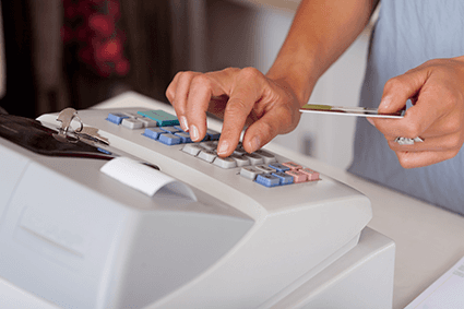 A cashier typing card details into a till