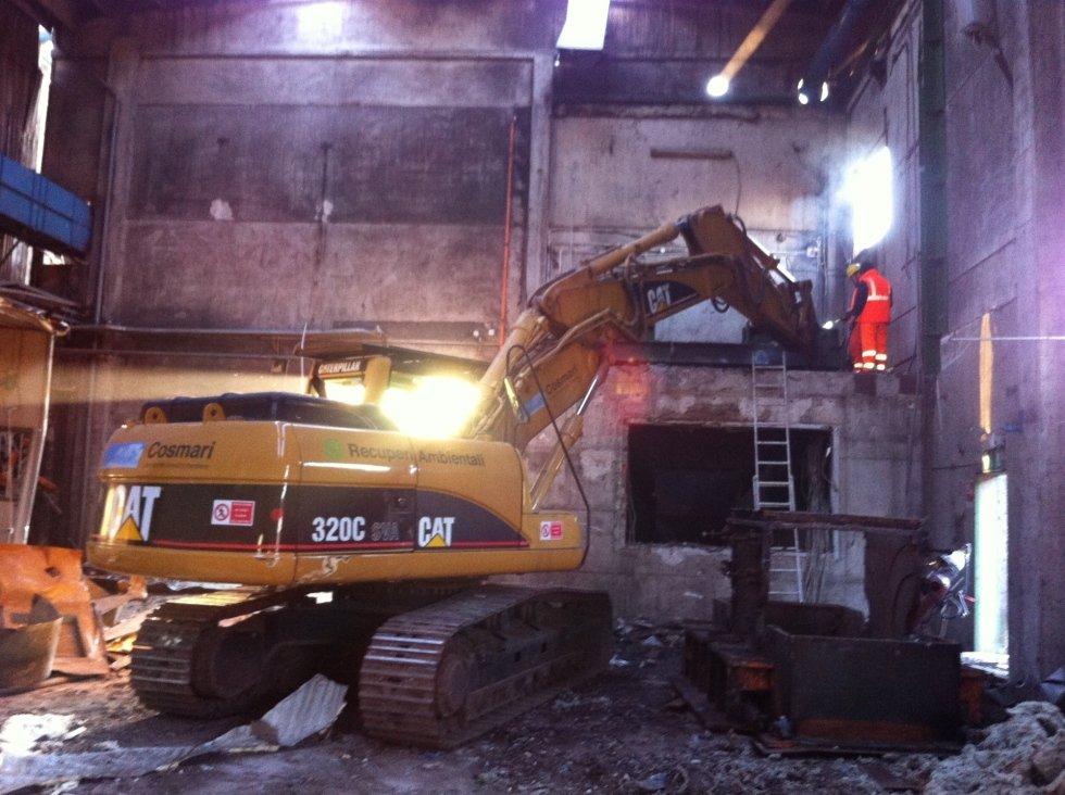 mezzo industriale impegnato nella demolizione all'interno di una struttura industriale