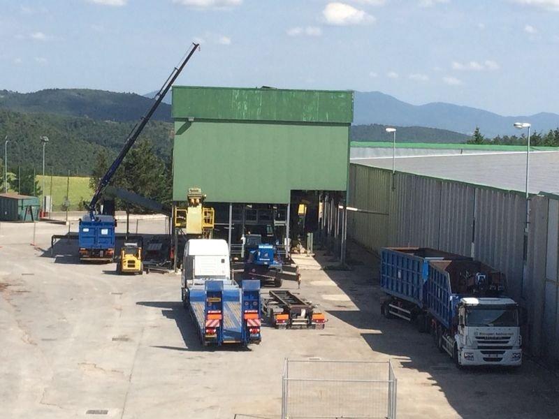 mezzi da demolizione nei pressi di un capannone
