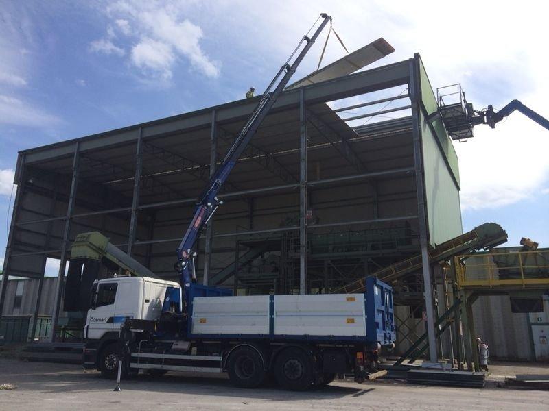gru impegnata nel recupero di materiale da una struttura industriale