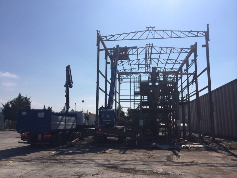 scheletro di struttura industriale con accanto un mezzo da demolizione