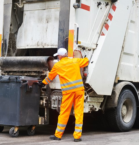 operaio in tuta arancione mentre aggancia un cassonetto al resto di un mezzo per la raccolta rifiuti