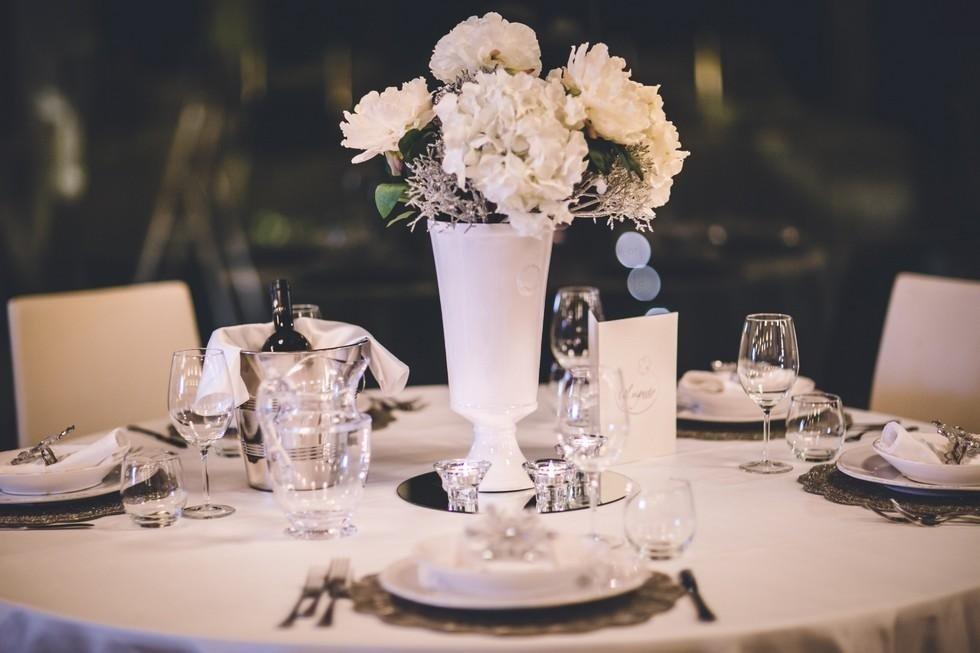 tavolo apparecchiato con centrotavola di fiori bianchi
