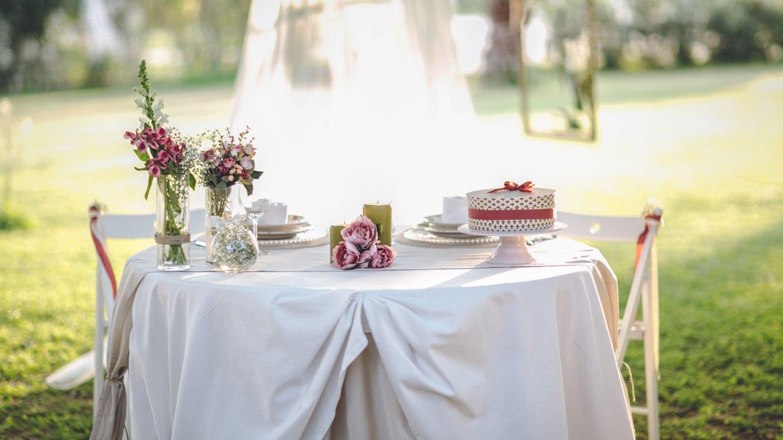 tavolino con vasi di fiori, centrotavola e torta su alzata