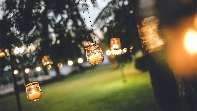 giardino con lanterne accese sugli alberi