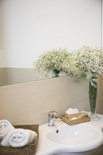 lavabo, fiori e cesta con asciugamano