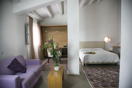 suite del resort con letto matrimoniale, divano, scrivania e poltrona
