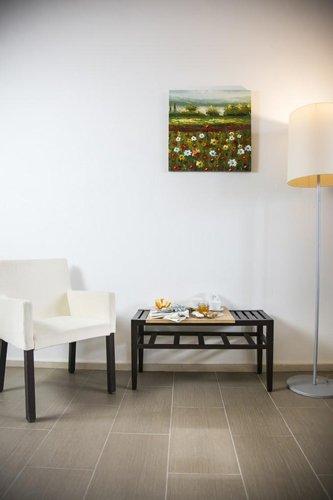 angolo colazione con poltrona, tavolino da caffè, piantana e quadro